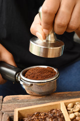 Freshly ground coffee beans in a metal filter on hand for background