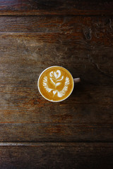 cup of latte art coffee on wooden background