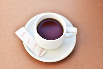 cup of coffee at morning on wooden table. subject is blurred.