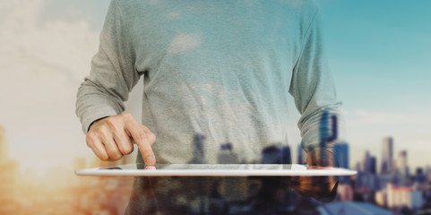 Asian guy using digital tablet with double exposure defocus city in sunrise background