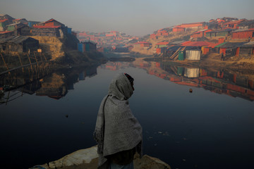 A Rohingya refugee stands next to a pond in the early morning at the Balukhali refugee camp near Cox's Bazar