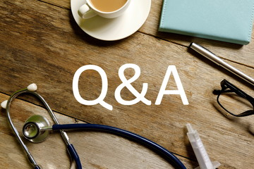 Healthcare and medical theme. Top view of stethoscope,a cup of coffee, notebook, pen,syringe and sunglasses on wooden background written with Q&A.