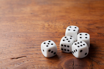 Game of chance concept. Gambling devices. White dice on rustic wooden board. Copy space for text.