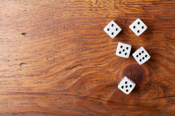 Heap of white dice on rustic wooden table top view. Gambling devices. Game of chance concept.