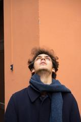 Cheerful young man at orange wall