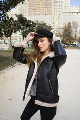 Stylish woman putting on cap