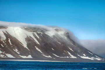 Cloud caught on the glacial sheet, nunatak in fog