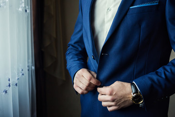 Businessman wears a jacket,male hands closeup,groom getting ready in the morning before wedding ceremony