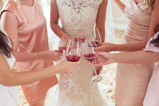 Bride and bridesmaids celebrate wedding day and drink rpink champagne from glasses together