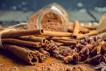 Cinnamon sticks on the rustic wooden background. Selective focus. Shallow depth of field. Toned image.