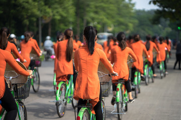 Vietnamese girls wear traditional long dress Ao Dai cycling on Hanoi street