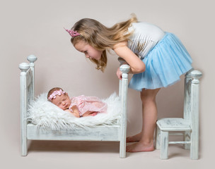 Little girl sits next her newborn sister