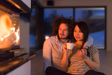 happy multiethnic couple sitting in front of fireplace