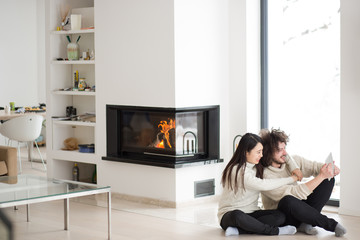 multiethnic couple using tablet computer in front of fireplace