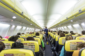 Interior of low priced commercial airplane with passengers on seats and stewardess walking the aisle.