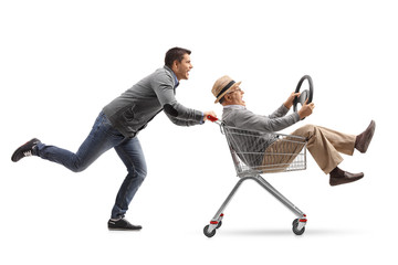 Young man pushing a shopping cart with a mature man riding inside