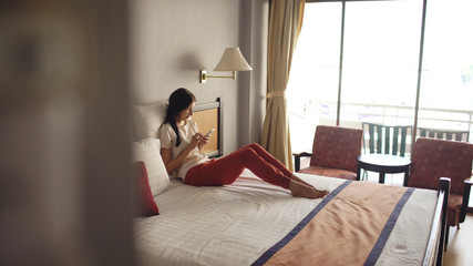 Pretty woman lying in bed in hotel room and using smartphone and smiling