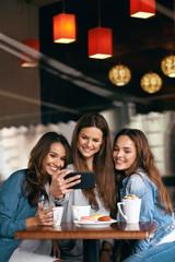 Beautiful Girls In Cafe Taking Selfie Photo On Phone.