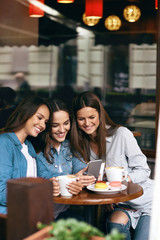 Young Female Friends Using Phone And Drinking Coffee In Cafe.