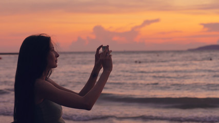 Young tourist woman photographs ocean view with smartphone during sunset at beach