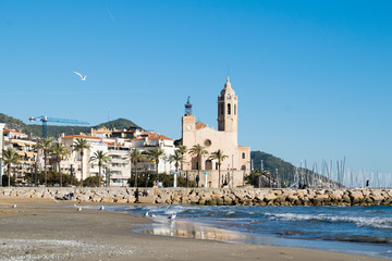 The beautiful town of Sitges with seagulls, winter Spain, Landscape of the coastline in Sitges, Parròquia de Sant Bartomeu i Santa Tecla