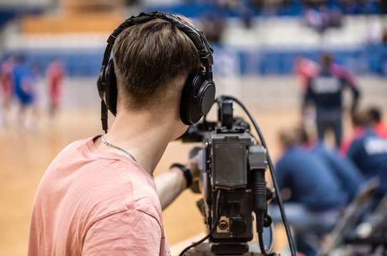 video operator recording a sports match on a professional video camera