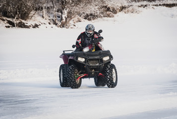 extreme Moto rider in gear on the ATV in the winter in the snow