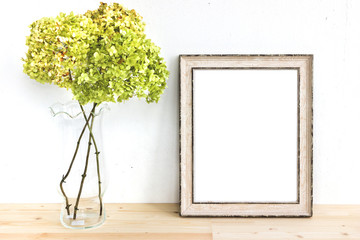 Wooden frame mockup with green flowers. Poster product design styled mock-up