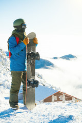 Winter sports concept - male snowboarder holding board in hands at the very top of a mountain - outdoors shot