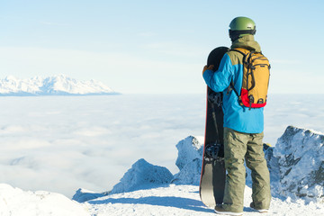 Winter sports concept - young male snowboarder holding board in hands at the very top of a mountain - outdoors shot