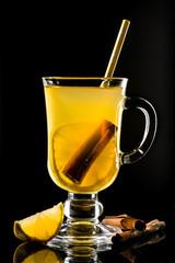 Hot grog with lemon, cinnamon sticks and honey Isolated on black background