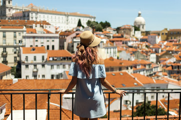 Young woman looking at Lisbon city panorama of Alfama on trip