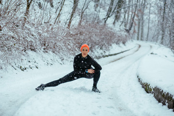 Woman wearing black and orange sportswear training exercising stretching legs outside during winter snowy day. Healthy lifestyle and cold weather concept.