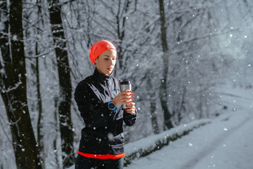 Woman athlete fit girl jogger wearing black sporty clothes outdoor in cold weather drinking hot tea from vacuum flask thermos cup, warming up. Sports, activities, running hiking in winter time.