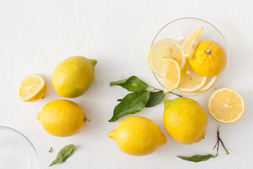 A bunch of lemons with leaves and sliced lemons on a white concrete background.