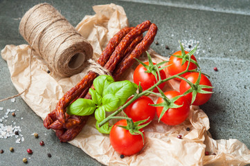 pork sausages and cherry tomatoes on a stone table
