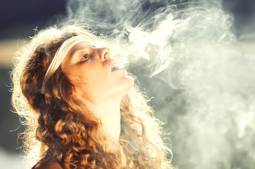 Beautiful free hippie girl blowing smoke - Vintage effect photo
