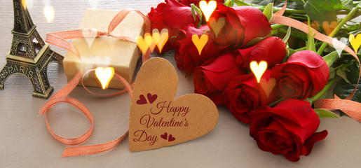 Valentine's day romantic background with beautiful bouquet of roses on wooden table.