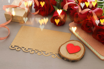 Valentine's day background. Beautiful bouquet of roses next to empty letter on wooden table.