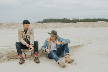 Hikers sitting on sand. Guys with a travel backpack in a fake desert in fotest.