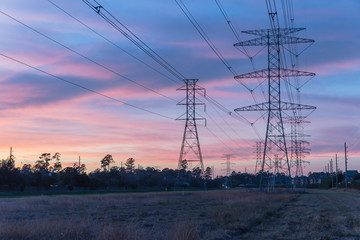 Industrial background group silhouette of transmission towers (or power tower, electricity pylon, steel lattice tower) at twilight in USA. Texture of high voltage pillar, overhead power lines at dusk