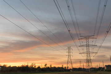 Industrial background group silhouette of transmission towers (or power tower, electricity pylon, steel lattice tower) at bloody red sunset. Texture of high voltage pillar, overhead power line at dusk