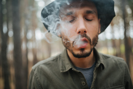 Man smoking cigarette, young hipster in hat and jacket at cloudy sky on natural background, copy space