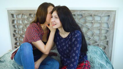 friends women blonde and brunette sitting bed whispering in ear secrets and smiling