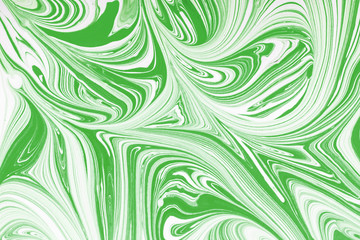 Green and white paint mixing together creating shapes background.