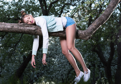 Wild fatigue. Beautiful young woman sleeping on a tree branch. Feet and hands hanging down