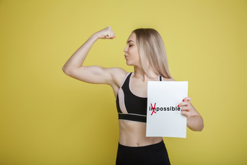 blond female athlete showing biceps on yellow background, holding white sheet with motivating inscription