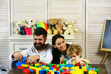 Parents and boy with smiling faces make brick constructions