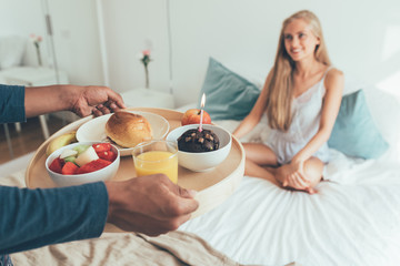 Young beautiful interracial couple having a surprise birthday breakfast in bed .