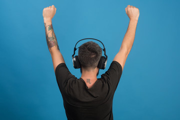 Dj with scorpio tattoo wears headphones, copy space.